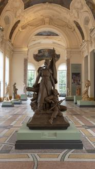 """Vue de la galerie de sculptures : au centre """"La Défense de Paris"""" de Barrias"""